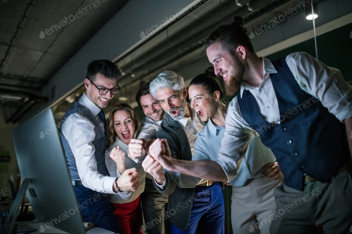 A group of business people with computer in an office, expressing excitement.