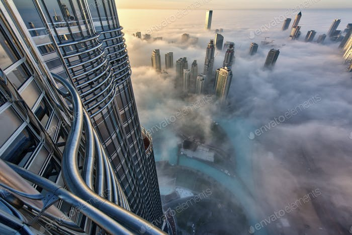 Aerial view of cityscape with skyscrapers above the clouds in Dubai, United Arab Emirates.