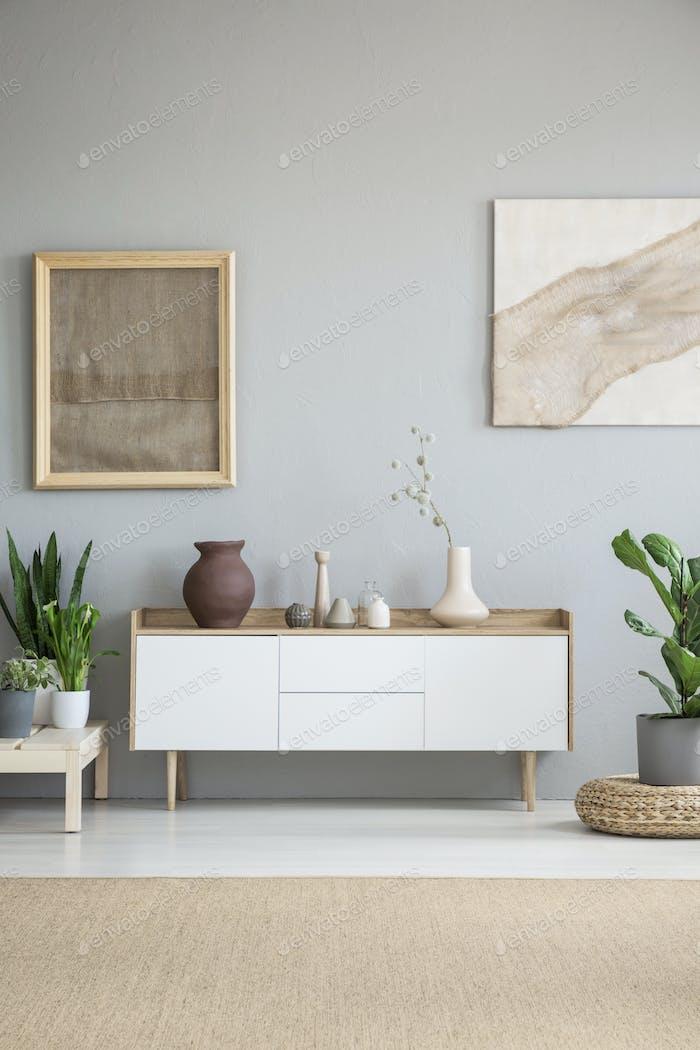 Weißer Schrank zwischen Pflanzen in grau Wohnzimmer Interieur mit