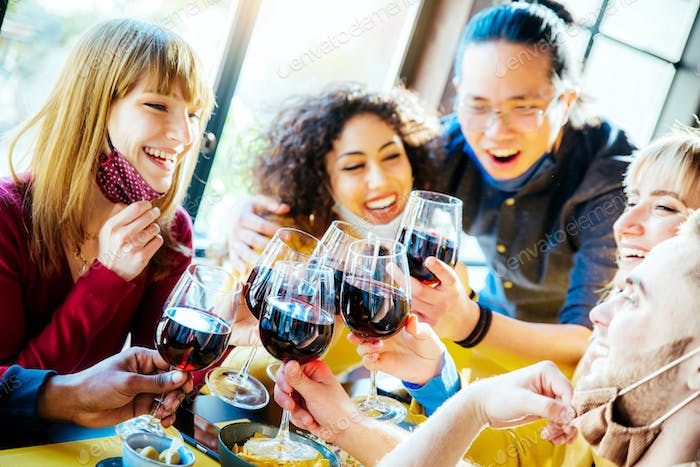 Happy friends wearing protective face masks toasting red wine sitting at bar restaurant