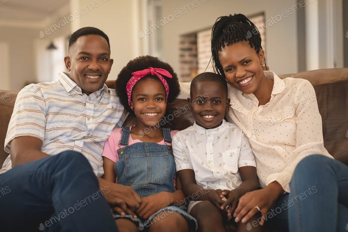 Happy African American family sitting on the sofa and looking at camera in a comfortable home