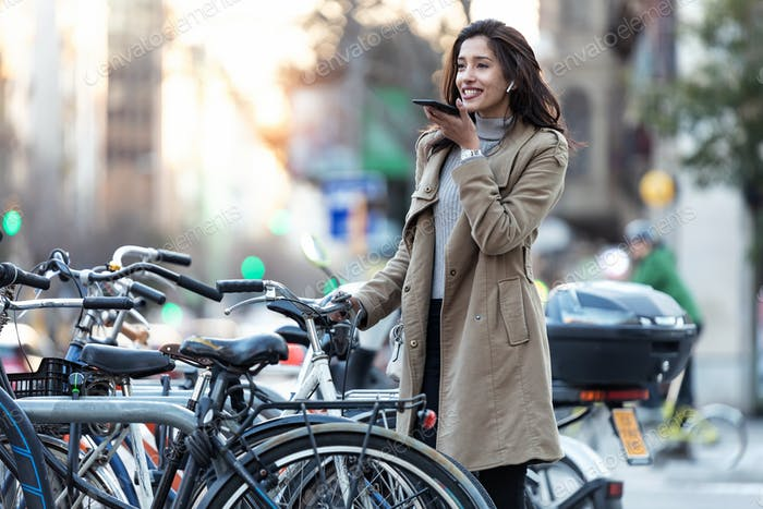 Pretty young woman using voice recognition system on her smartphone while standing in the street.