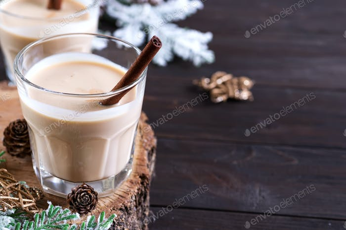 Eggnog Christmas milk cocktail, served in two glasses on a wood cutting board with fir branch and