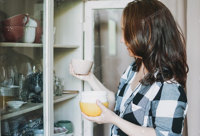 Smiling adult woman in casual plaid shirt takes dishes from vintage sideboard at home