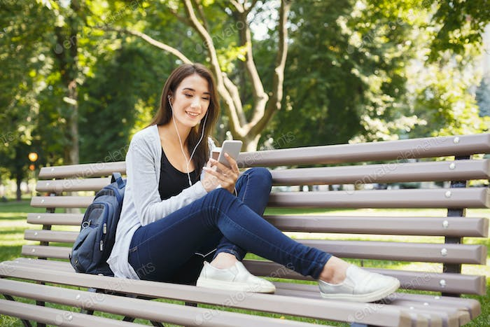Student sitting in park and using smartphone