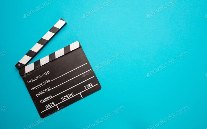 Movie clapperboard on blue color background, top view