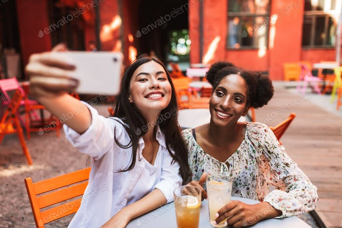 Cheerful girls sitting at table with cocktails taking photos on