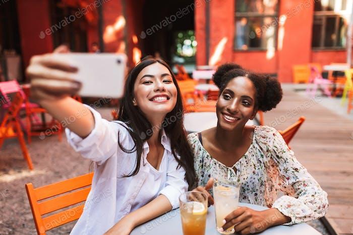 Fröhliche Mädchen sitzen am Tisch mit Cocktails, die Fotos machen