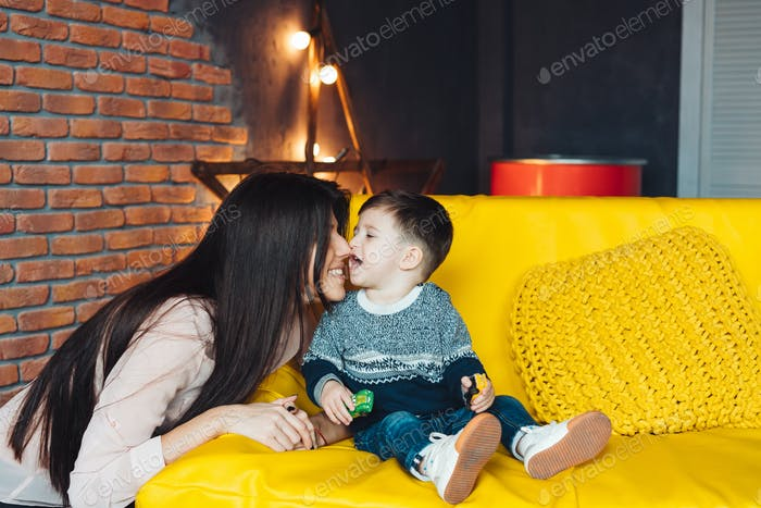 Mother and little son play at home