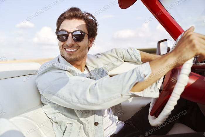 Handsome man behind the wheel of an old school car