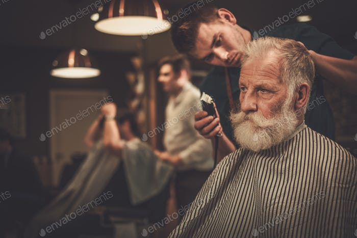 Confident senior man visiting hairstylist in barber shop.