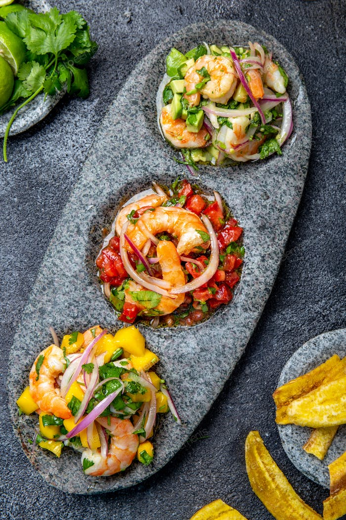 Three colorful shrimps ceviche with mango, avocado and tomatoes.