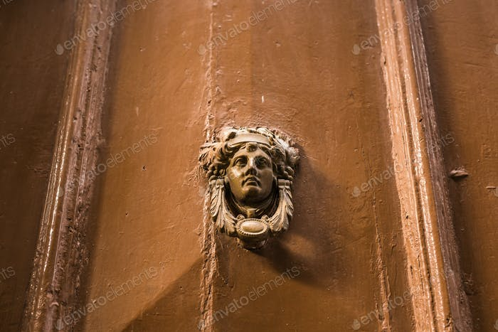 Traditional ornate door handle or knocker against a wooden door