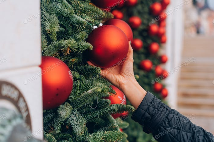 Hand decorating Christmas tree with red baubles