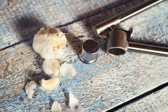 Garlic press and cloves of garlic
