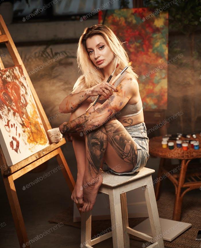 Glamour female painter with paintbrushes cuddling legs