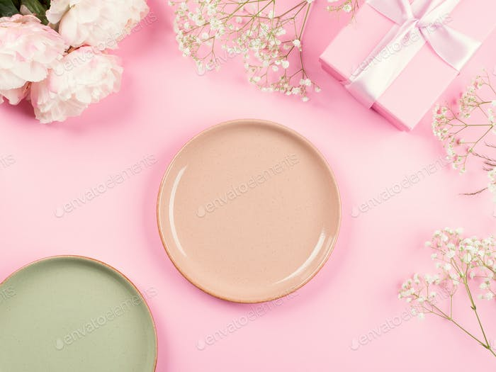 Pink pastel background with flowers, empty plates
