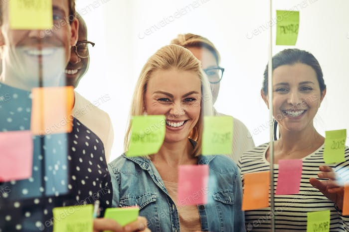 Group of laughing office colleagues brainstorming with sticky notes