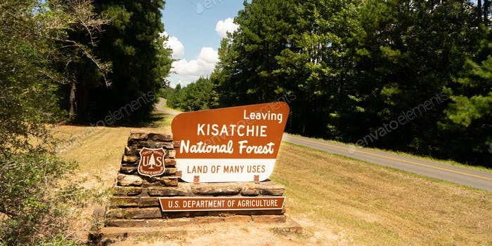 Two lane road passes exit sign to Kisatchie National Forest