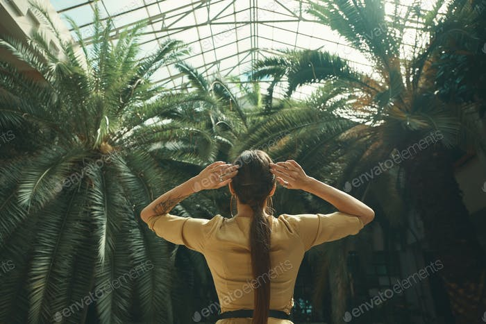Back view fit exotic woman watching palm trees in a tropical gar