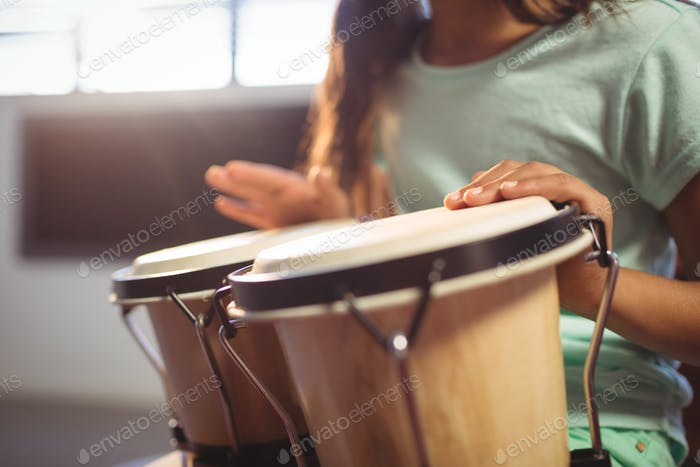 Mid section of girl playing bongo drums in classroom