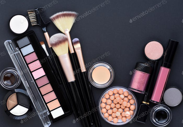 Makeup brush and decorative cosmetics on black background. Minim