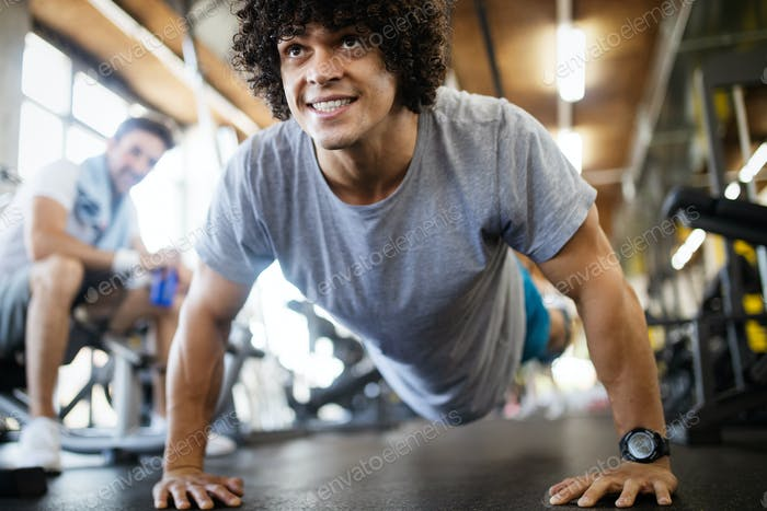 Portrait of a handsome man doing push ups exercise in gym