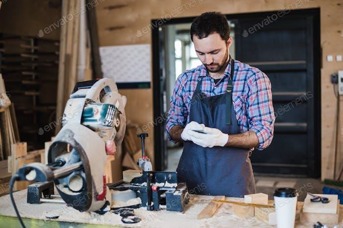 carpintero enviando mensajes de texto a alguien en su teléfono Inteligente cerca de la sierra circular en un taller polvoriento