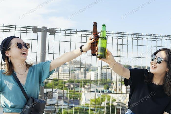 Zwei junge japanische Frauen sitzen auf einem Dach in einer städtischen Umgebung und trinken Bier.