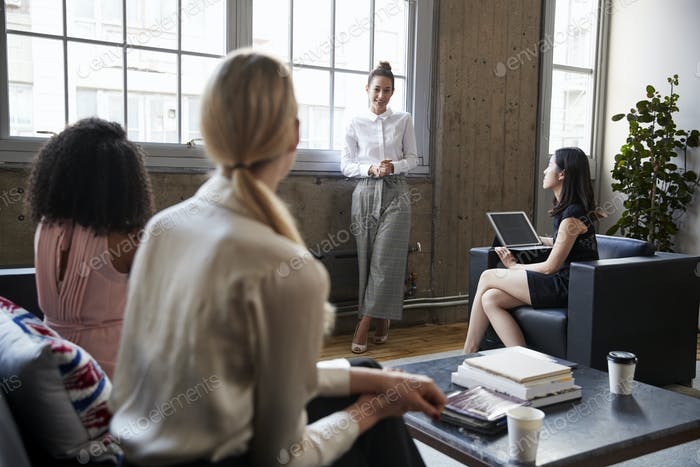 Standing female manager talking to team at casual meeting
