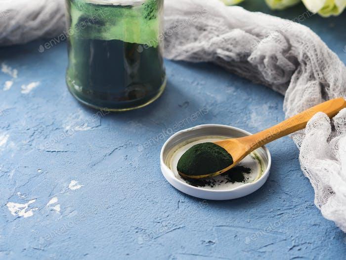 Spirulina powder on blue background