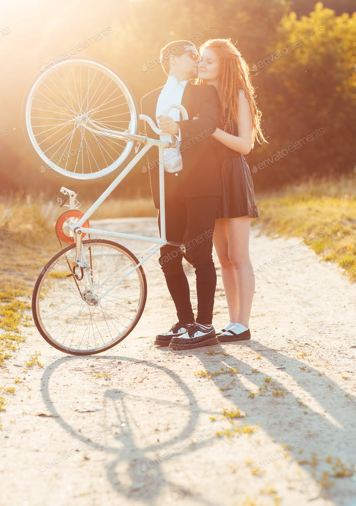 Guy with the girl and bicycle outdoors