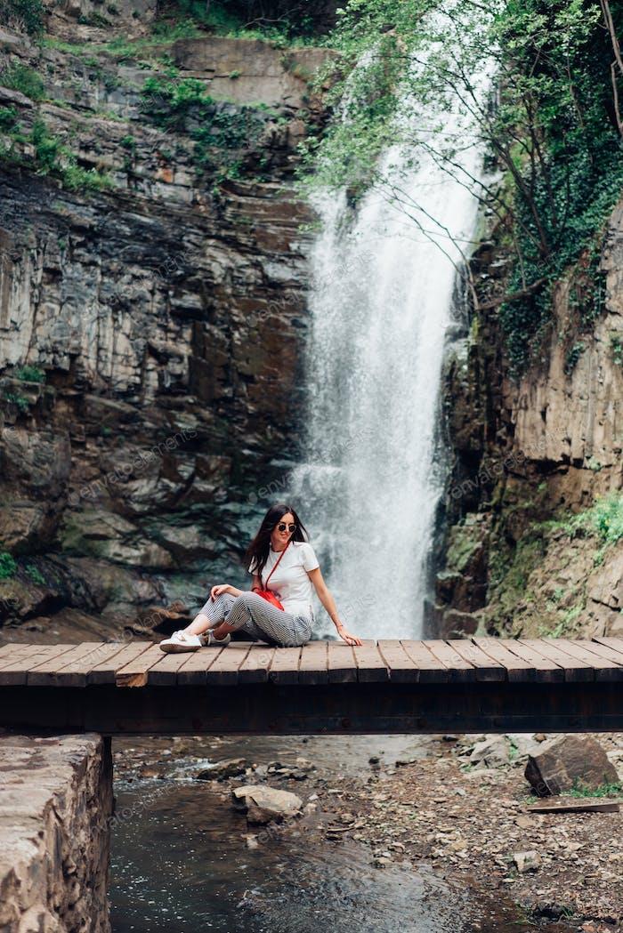 The girl sits on a bridge