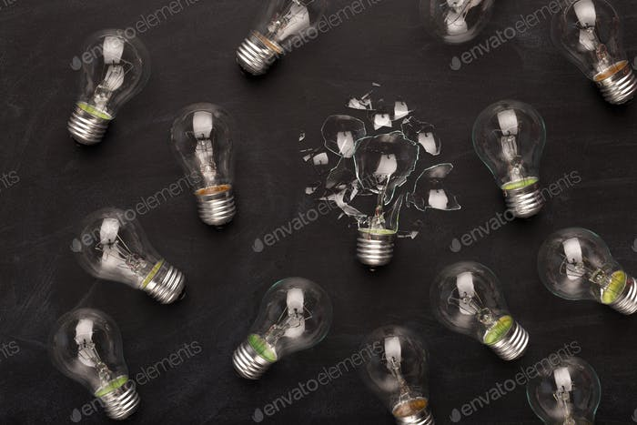 Whole and broken light bulbs on black background