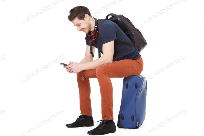 happy male traveler sitting on suitcase and looking at cellphone