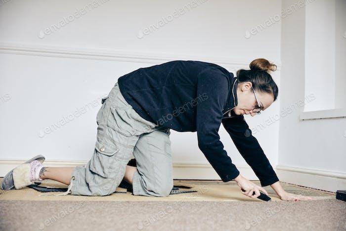 Frau mit Messer zu schneiden Teppich auf dem Boden