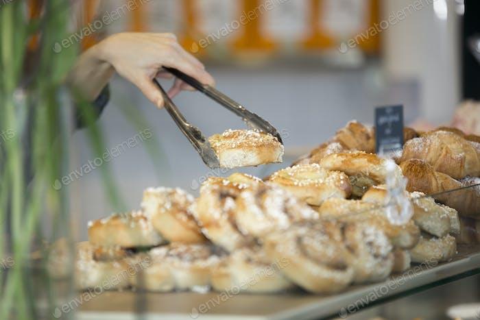 Anbieter serviert süße Brötchen mit Zange