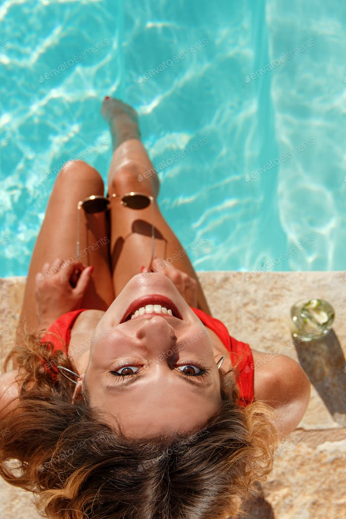 Young woman with legs in a swimming pool with sunglasses in hand