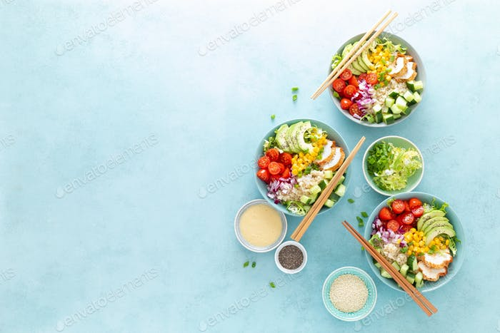 Lunch bowls with grilled cgicken meat, rice and fresh salad of avocado, cucumbers, corn