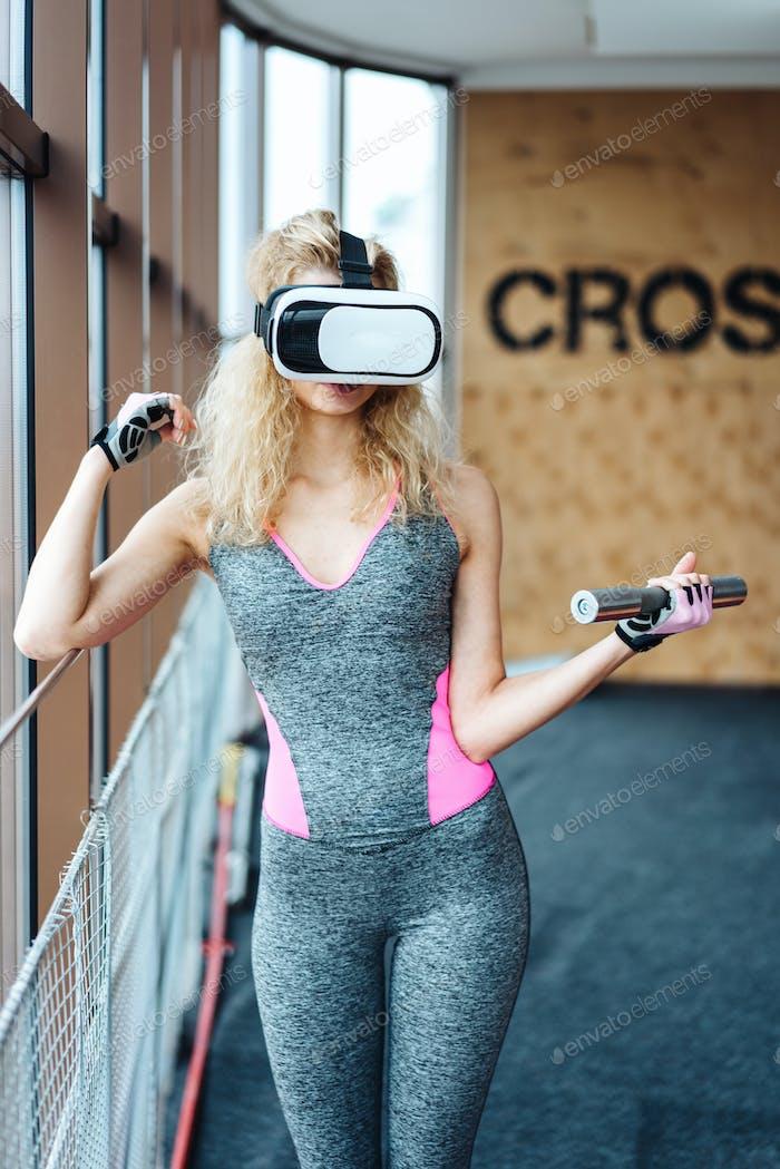Schönes Mädchen im Fitnessstudio mit VR-Headset