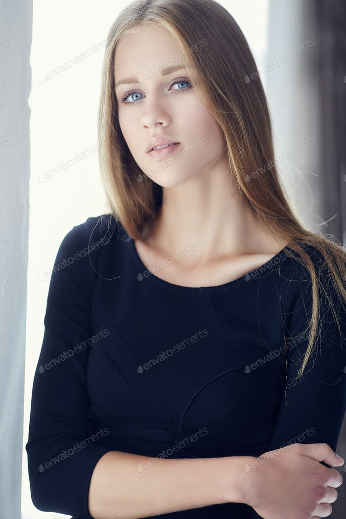 Young woman with blue eyes  in a black dress.