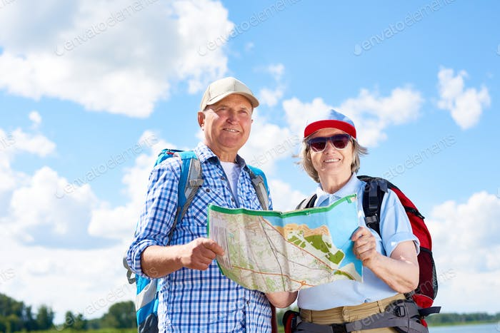 Happy Senior Tourists Posing with Map