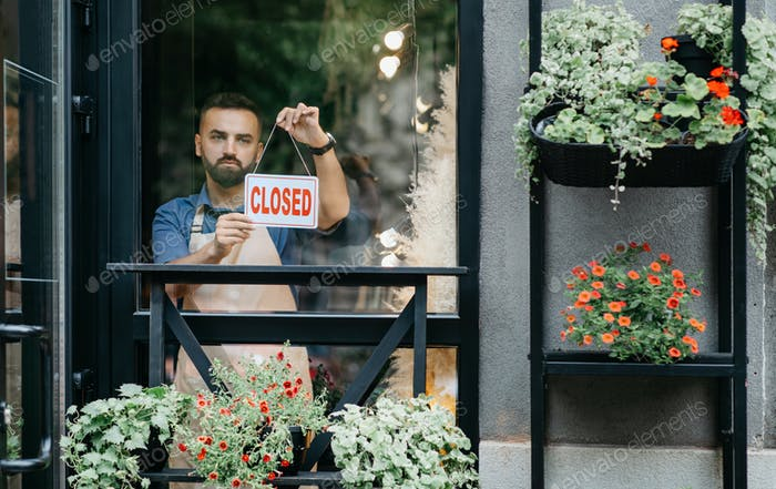 Pequeña empresa, propietario del estudio de flores cierra tienda al final del día y cierre Covid-19
