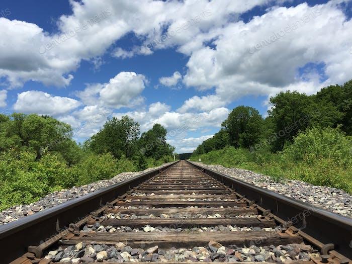 Eisenbahn zum Horizont und Wolken auf dem Hintergrund des Himmels.