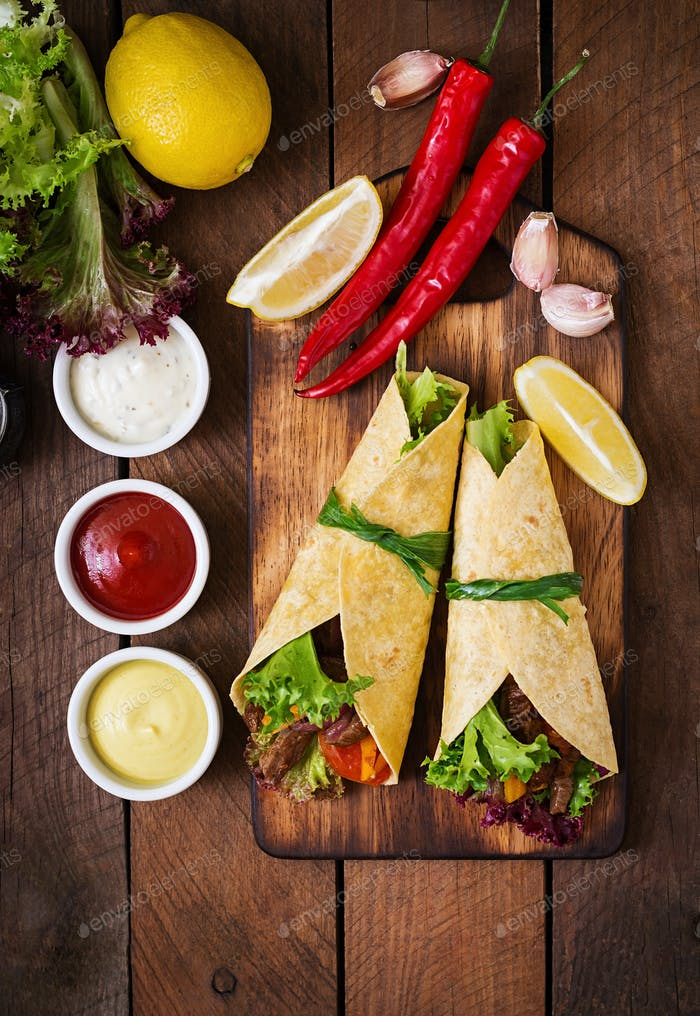 Mexican fajitas for beef and grilled vegetables (paprika, red onion, tomato). Top view