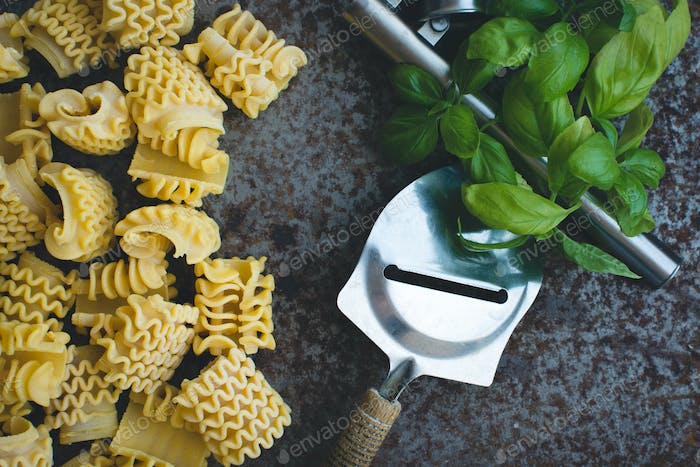 Pasta with cheese grater and basil on a rusty metallic background