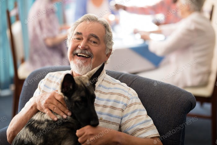 Portrait of smiling senior man sitting with puppy on chair