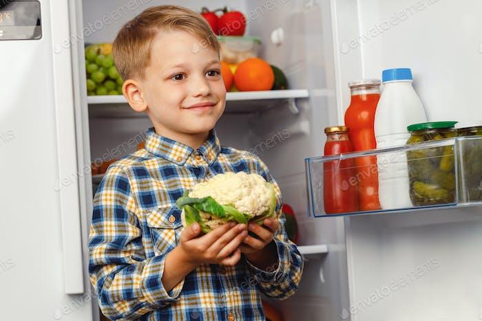 Little boy standing near the open fridge