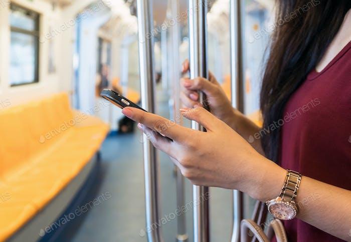 Крупным планом женщина с помощью смартфона в BTS Skytrain рельсы или MRT метро