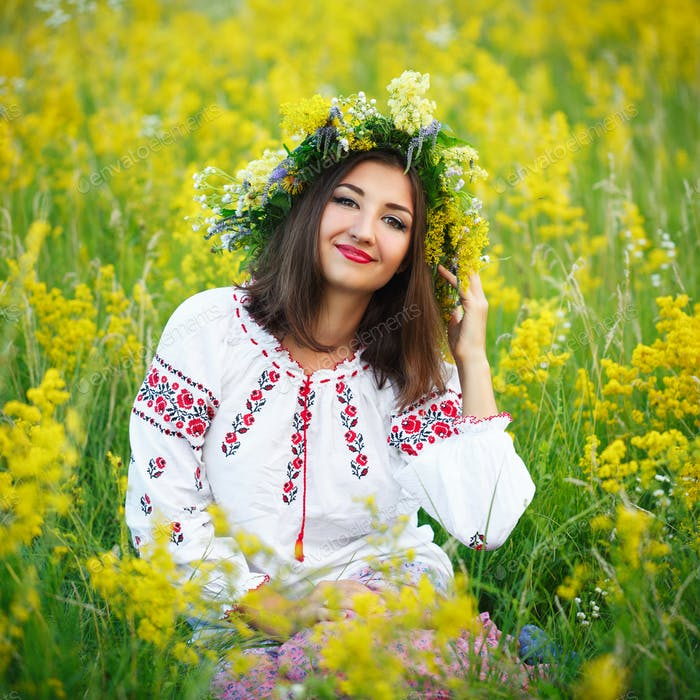 Young beautiful smiling girl in Ukrainian costume with a wreath
